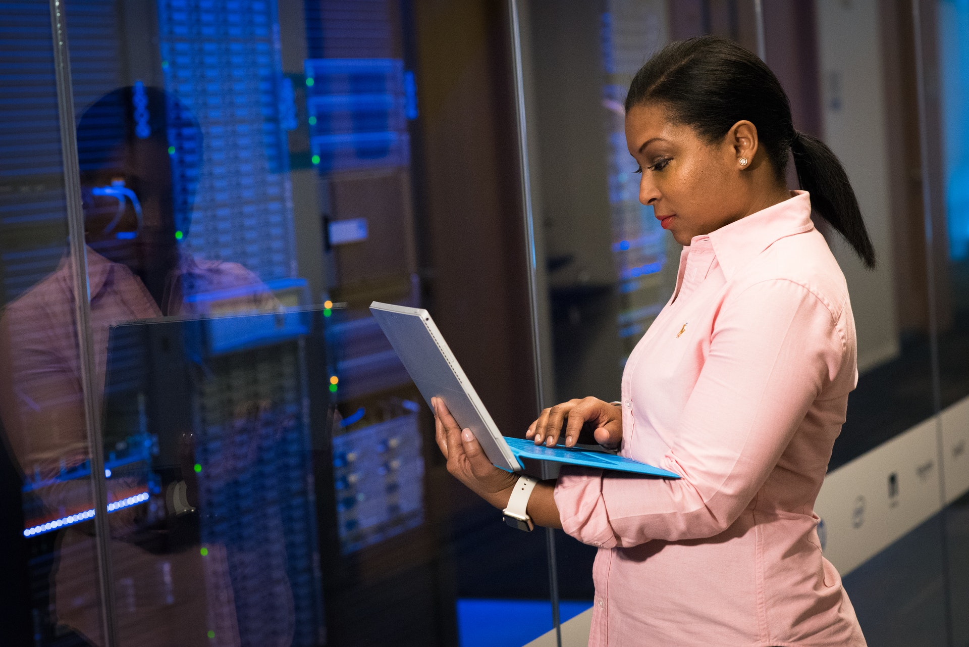 Woman standing with laptop in front of server