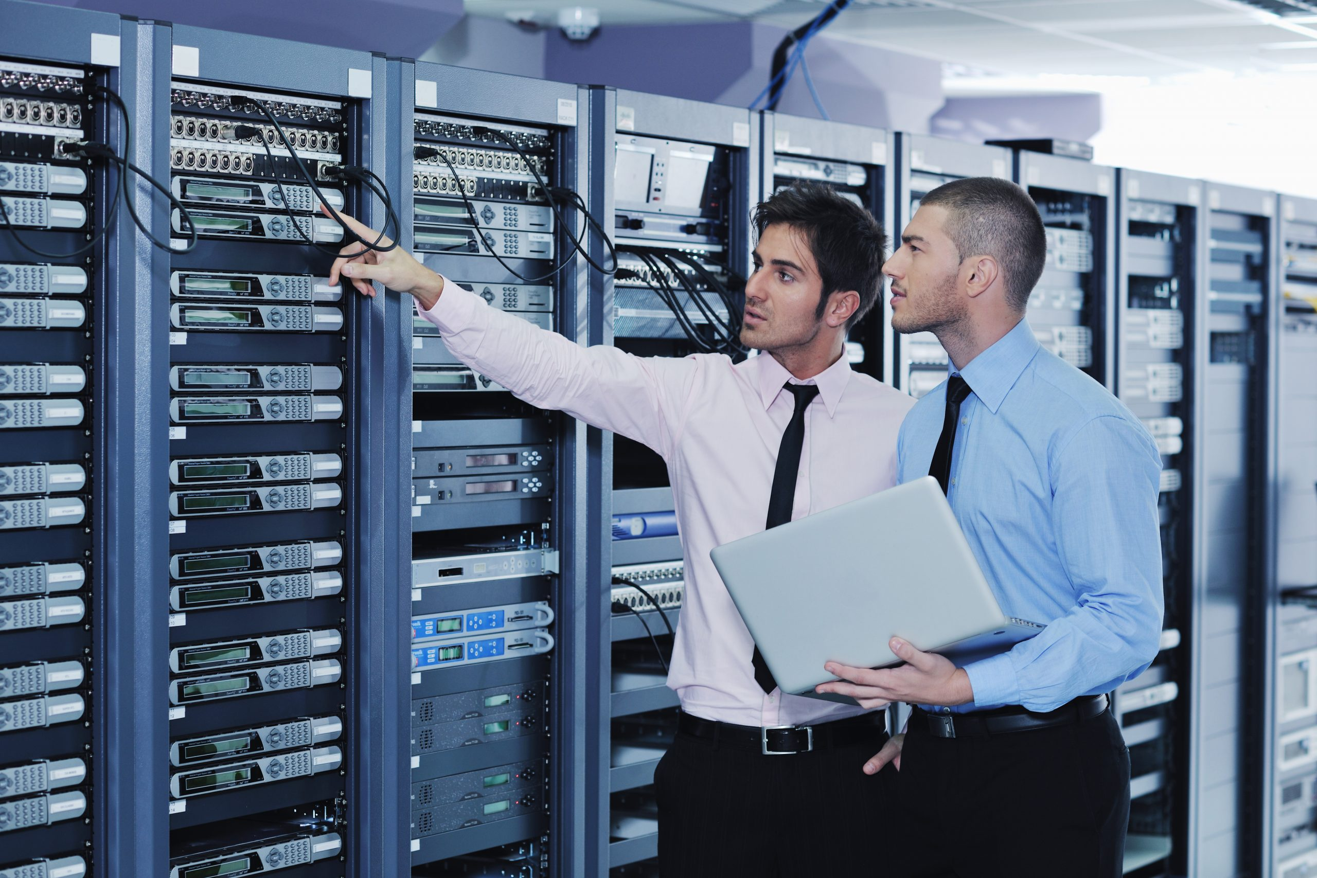 Two men with laptop in server room