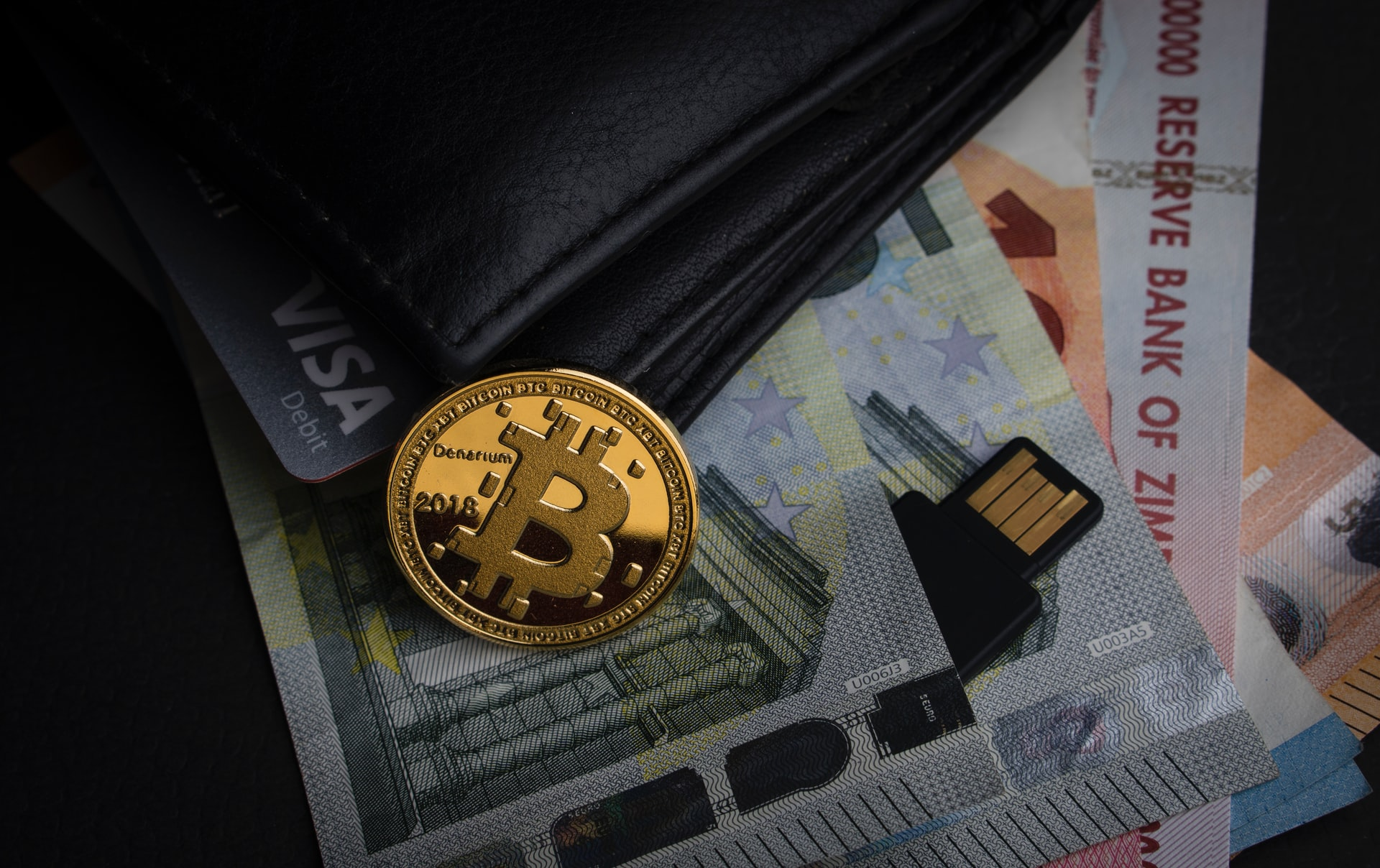 Wallet with money and a bitcoin