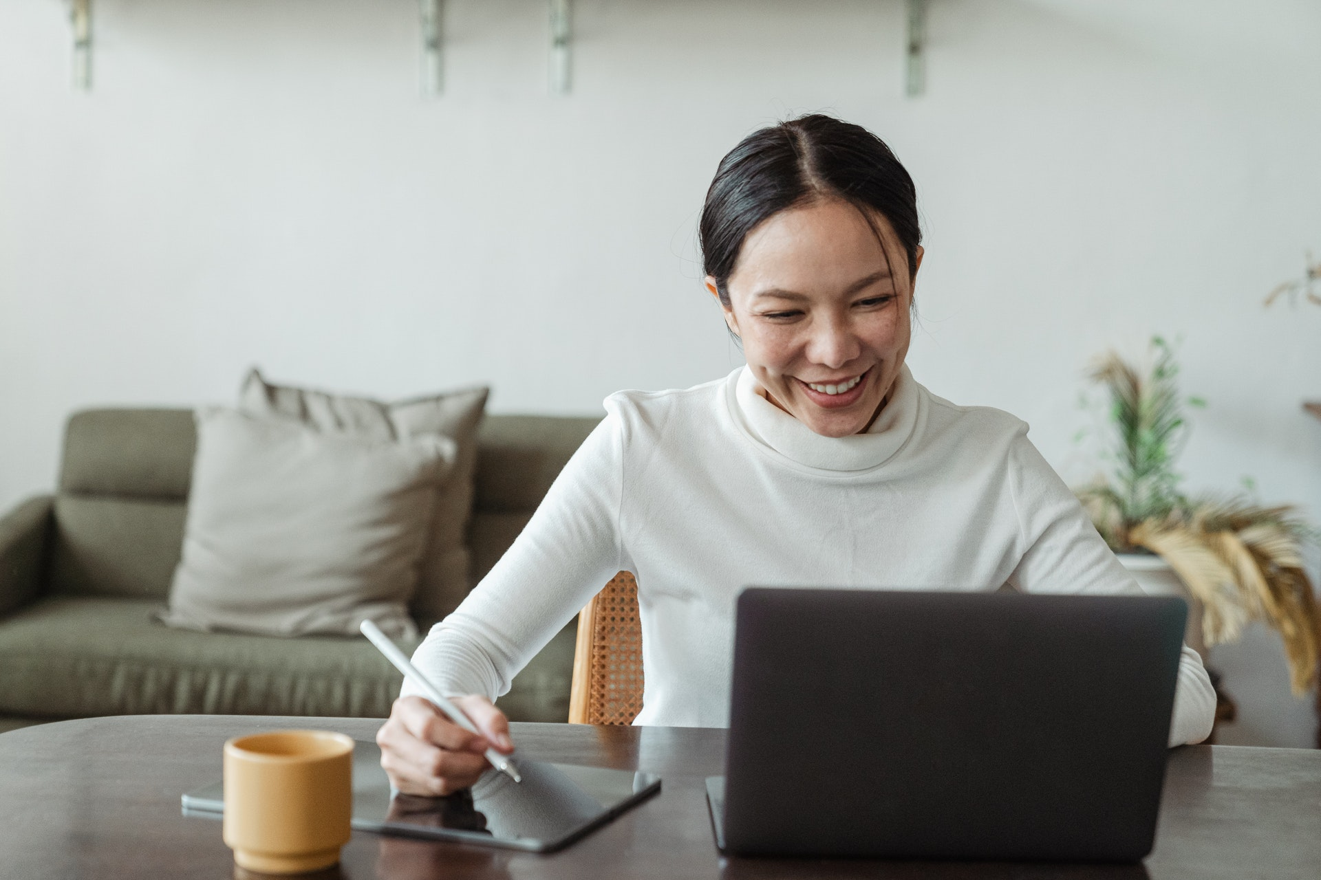 Woman happily looking at laptop