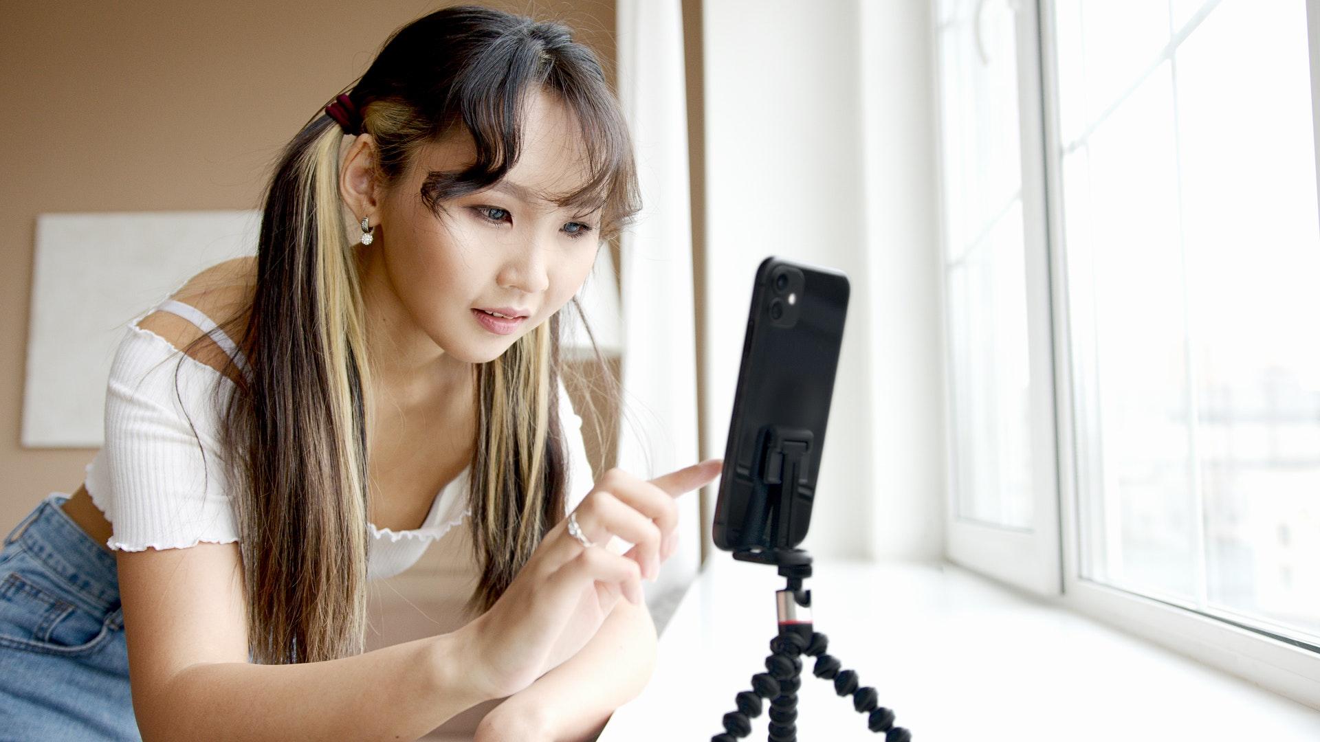 Girl using phone on tripod