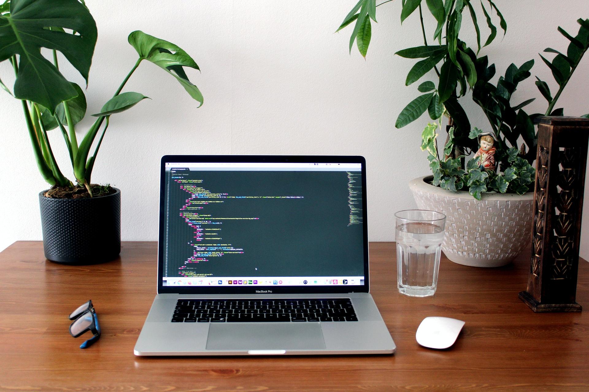 Laptop showing code editor on desk
