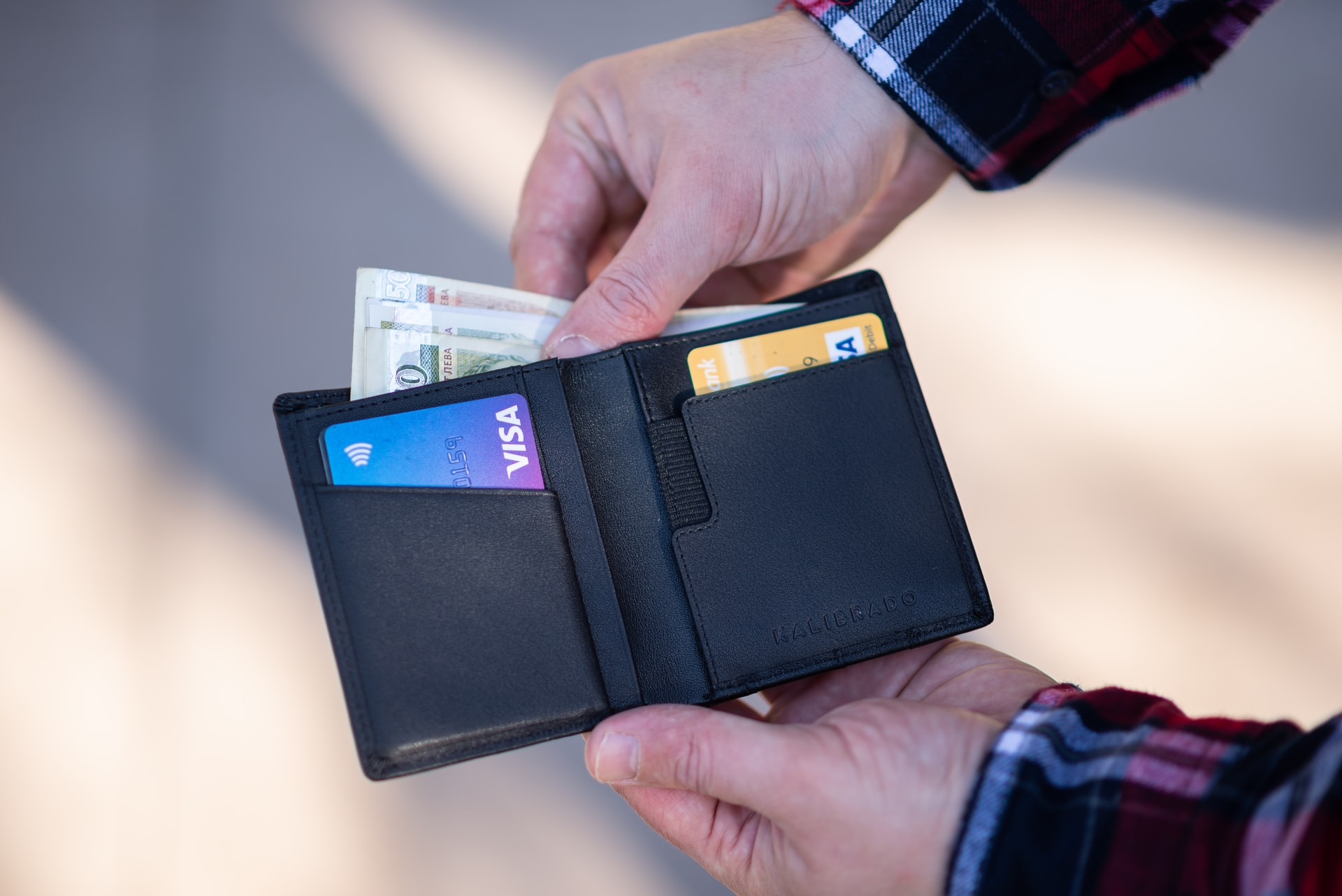 Person taking money out of wallet